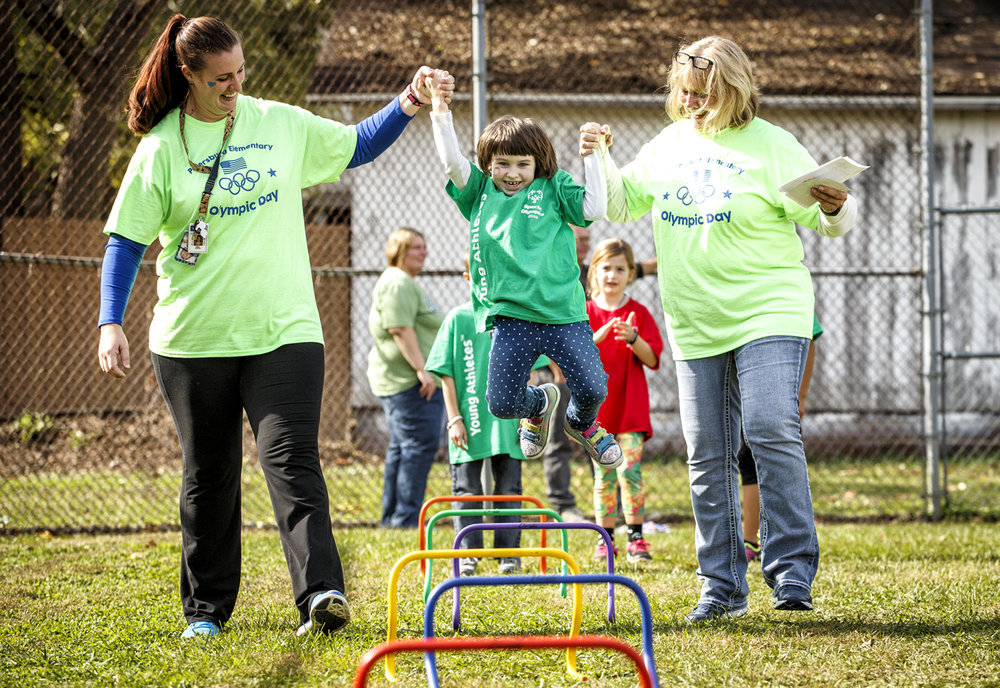 Katelyn Miller, 7, center, gets an assist from special education aid Lindsey Shaub, left, and individual aid Carmen Jackson, right, will navigating the obstacle course during the Special Olympics Young Athletes program at Petersburg Elementary School, Friday, Oct. 28, 2016, in Petersburg, Ill. Students with and without intellectual disabilities participated in the event that involved stations that used skills in running, jumping, throwing, striking kicking and catching. Justin L. Fowler/The State Journal-Register