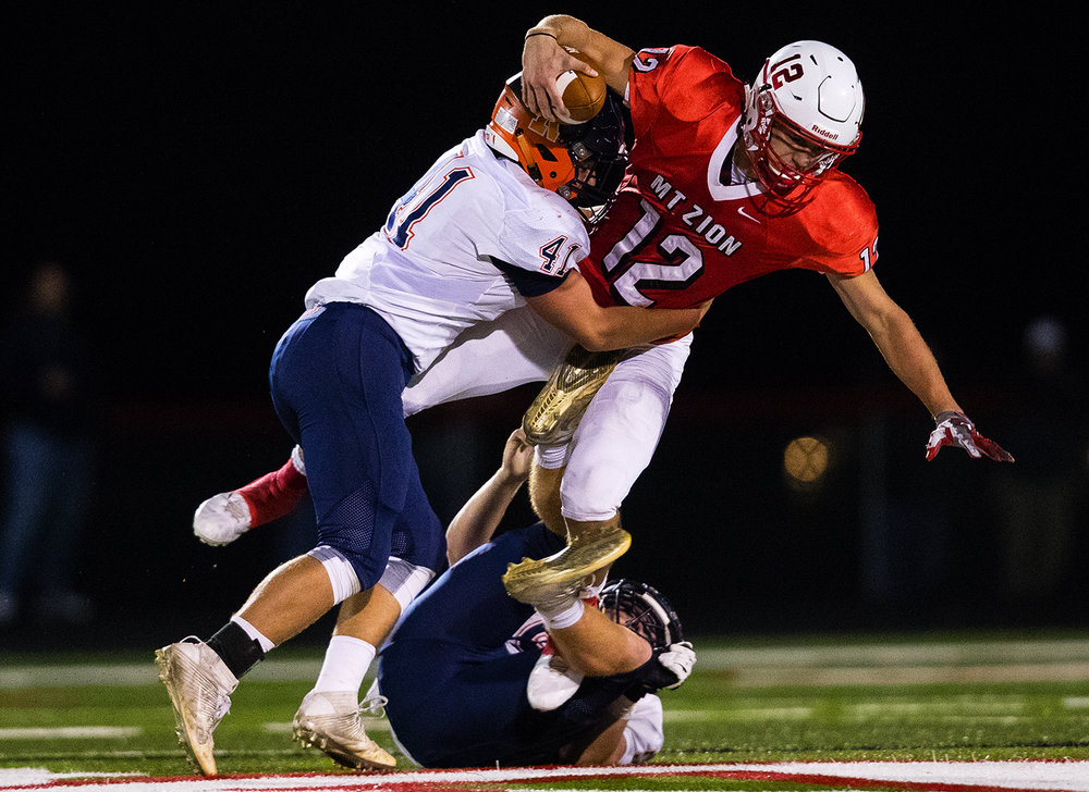 Rochester's Nick Capriotti sacks Mt. Zion's Brandon Price during the Class 4A playoff game at Mt. Zion Friday, Nov. 4, 2016. Ted Schurter/The State Journal-Register