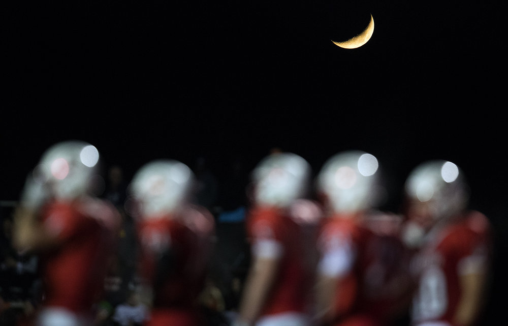 A crescent moon hangs in the air behind the Mt. Zion line as they face Rochester  during the Class 4A playoff game at Mt. Zion Friday, Nov. 4, 2016. Ted Schurter/The State Journal-Register