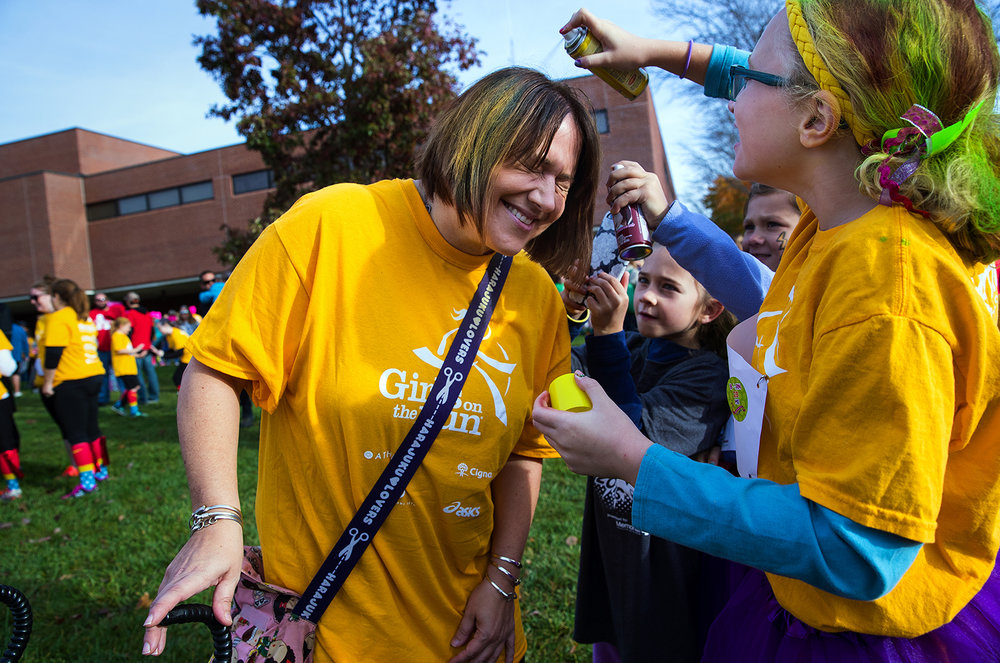 "Anne Madonia closes her eyes as girls on her Christ the King team spray color into her hair before the Girls on the Run ""Be Your Own Super Hero"" 5k on the campus of Lincoln Land Community College Saturday, Nov. 5, 2016. The run is the culmination of a 10-week program which focuses on teaching self-respect and healthy lifestyle choices. Ted Schurter/The State Journal-Register"