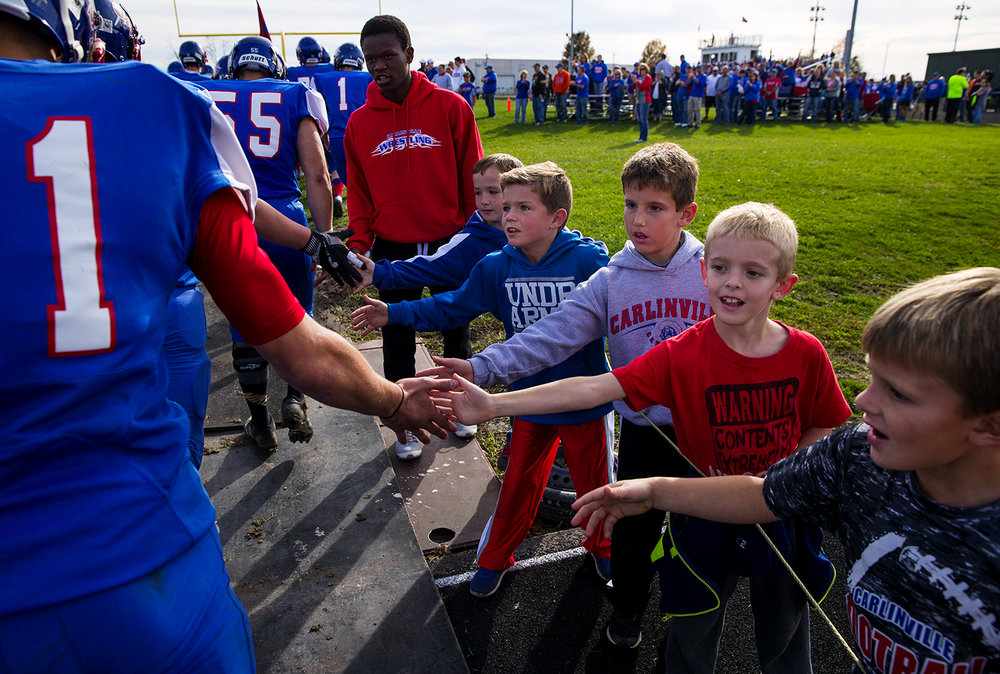 Carlinville fans high five the players as they take the field to face Williamsville during the class 3A football playoffs at Carlinville High School Saturday, Nov. 5, 2016. Ted Schurter/The State Journal-Register