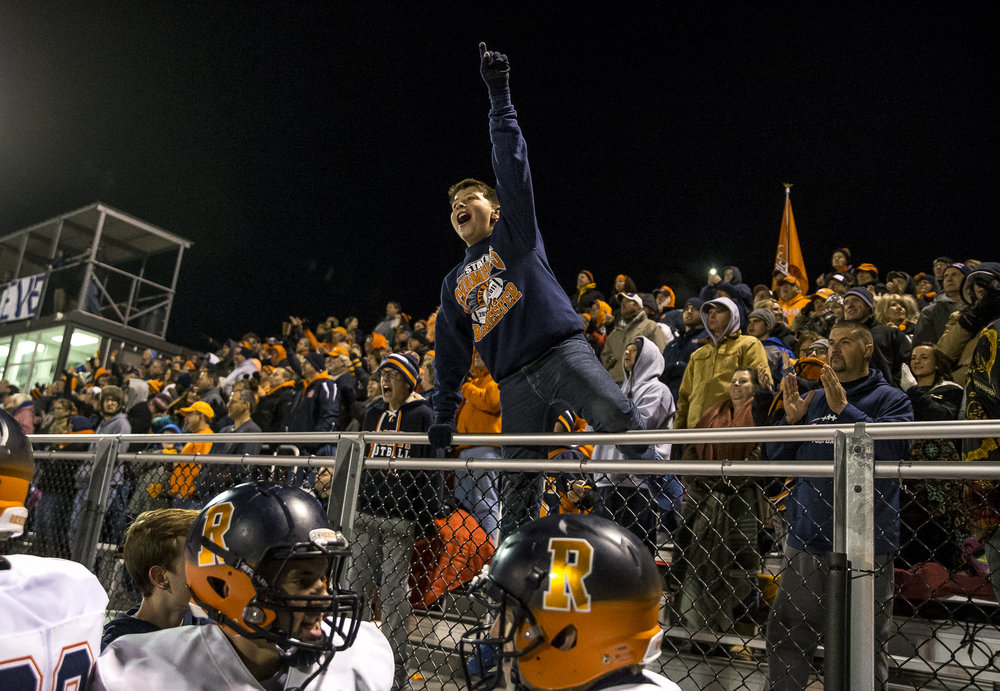Ian Lichtenberger, 11, leaps up on the fence to cheer on the Rockets as they try to hold off Belleville Althoff with a 48-47 lead in the final seconds in the second half of a IHSA Class 4A quarterfinal playoff game at Lindenwood Stadium, Saturday, Nov. 12, 2016, in Belleville, Ill. Justin L. Fowler/The State Journal-Register