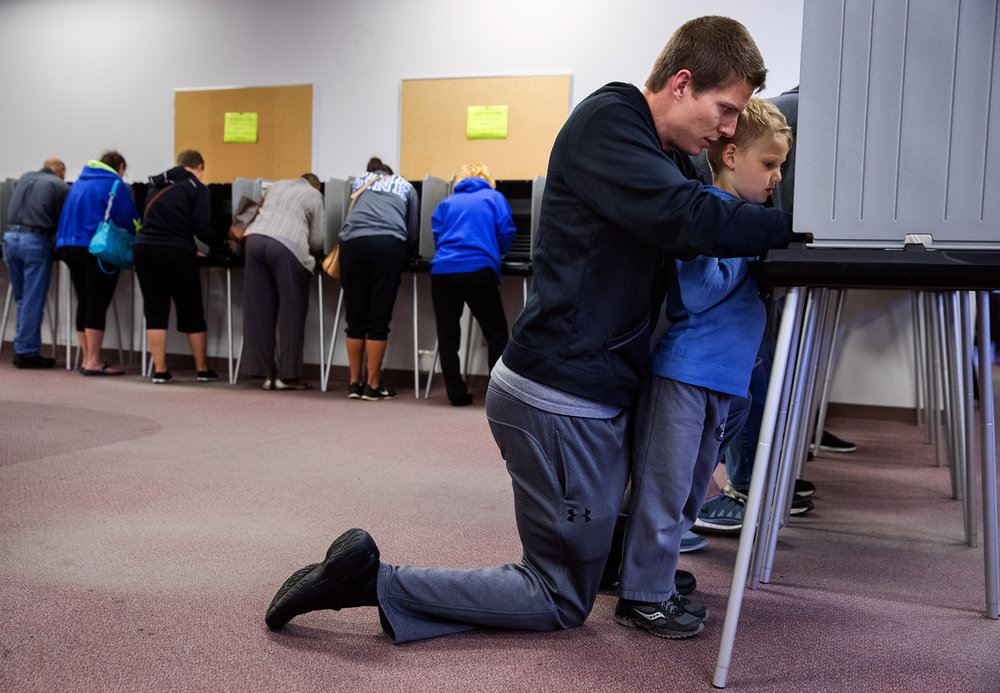 Ted Clark  kneels down in the voting booth so his five-year-old son Dane can watch him fill out his ballot at the  Sangamon County Building Sunday, Nov. 6, 2016. Clark said his son has been learning about the election at school and has excitedly been talking about it a long time. Ted Schurter/The State Journal-Register