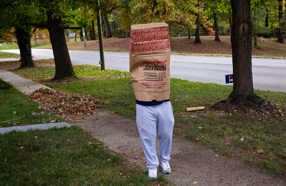 Roberto Flores strolls about with a leaf bag over his head as he rakes leaves with a group of his friends from the University of Illinois Springfield Sunday, Oct. 30, 2016. Ted Schurter/The State Journal-Register
