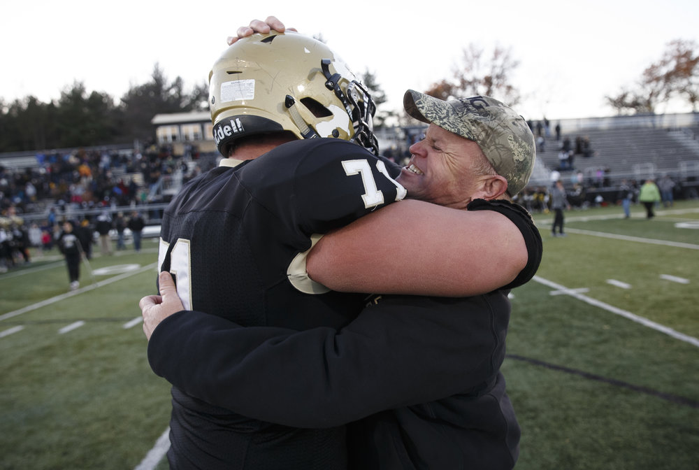 Sacred Heart-Griffin defensive coordinator Jim McMann celebrates with Sacred Heart-Griffin's John Pempek (71) after the Cyclones defeated Burbank St. Laurence in the IHSA Class 6A semifinals at the SHG Sports Complex, Saturday, Nov. 19, 2016, in Springfield, Ill. Justin L. Fowler/The State Journal-Register