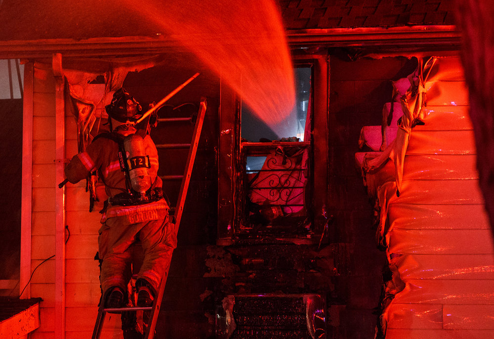 A Springfield firefighter works the exterior of a two-story home as water is shot through the window from the inside as they extinguish hot spots in the structure on the 1000 block of Reservoir Street, Thursday, Nov. 17, 2016, in Springfield, Ill. Justin L. Fowler/The State Journal-Register