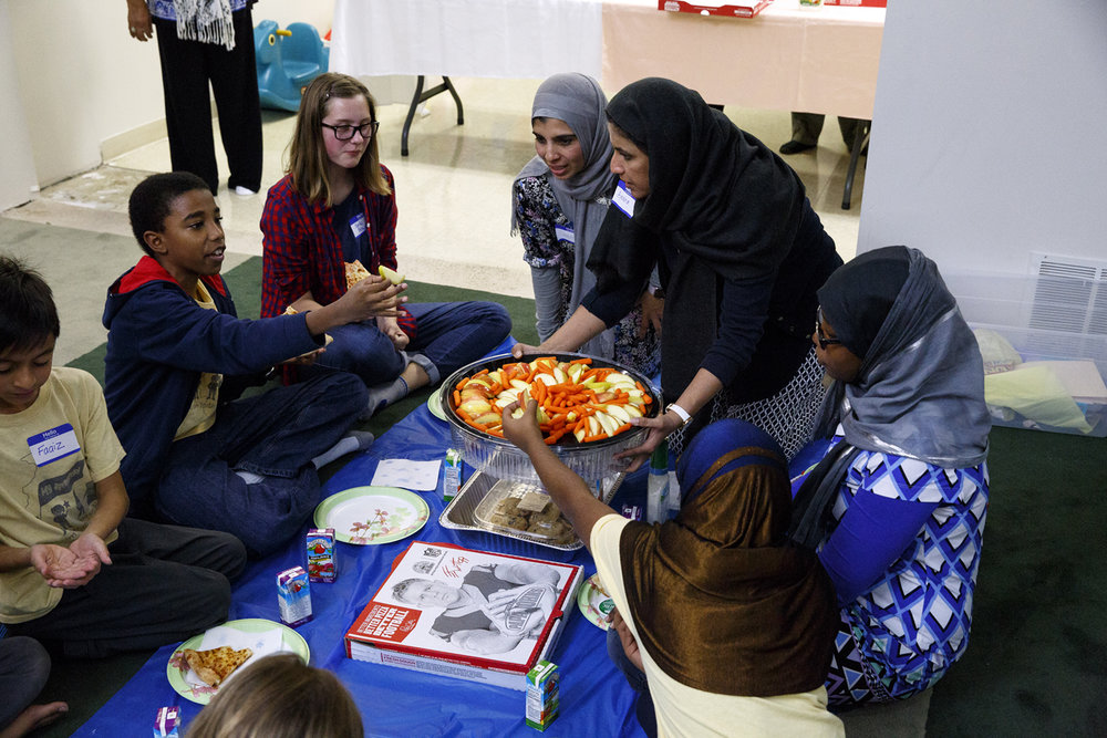 Ayesha Ahmad passes a fruit and vegetable tray during the meal at the Children of Abraham program at the Islamic Society of Greater Springfield mosque Wednesday, Nov. 16, 2016. The gatherings bring together kids from different faiths to build bridges and friendships at a young age. Rich Saal/The State Journal-Register