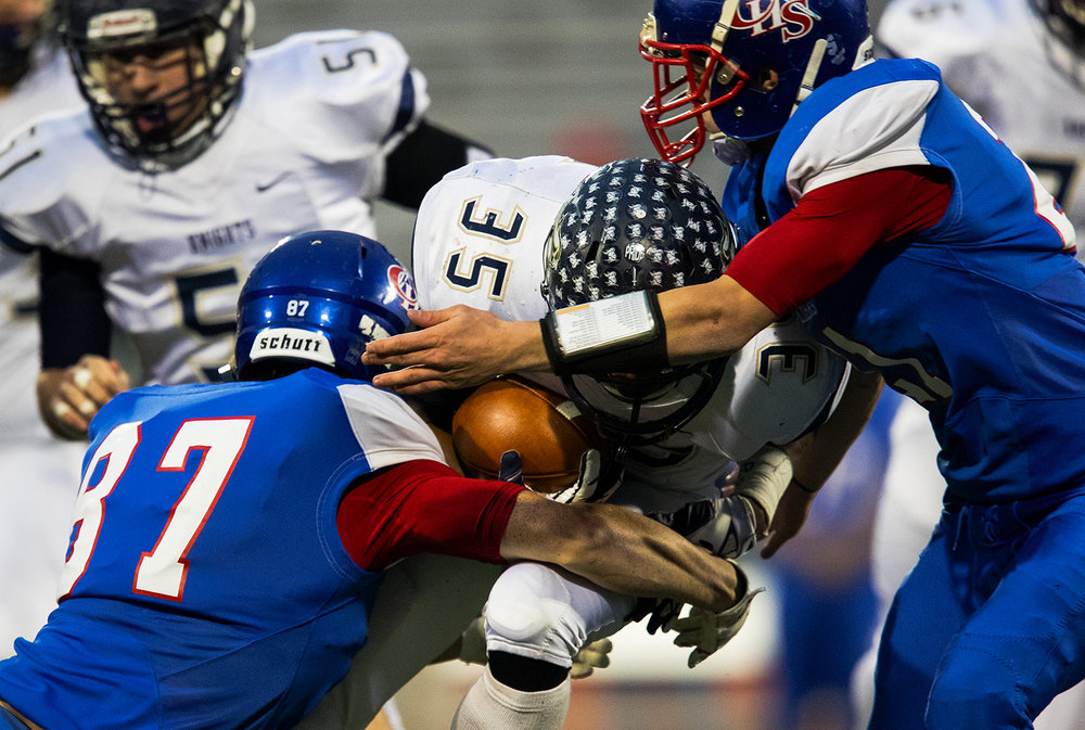 Carlinville's Brady Egelhoff (87) and Jacob Dixon (21) try to wrap up Elmhurst's Jordan Rowell during the Class 3A championship game at Memorial Stadium in Champaign, Ill., Friday, Nov. 25, 2016. Ted Schurter/The State Journal-Register