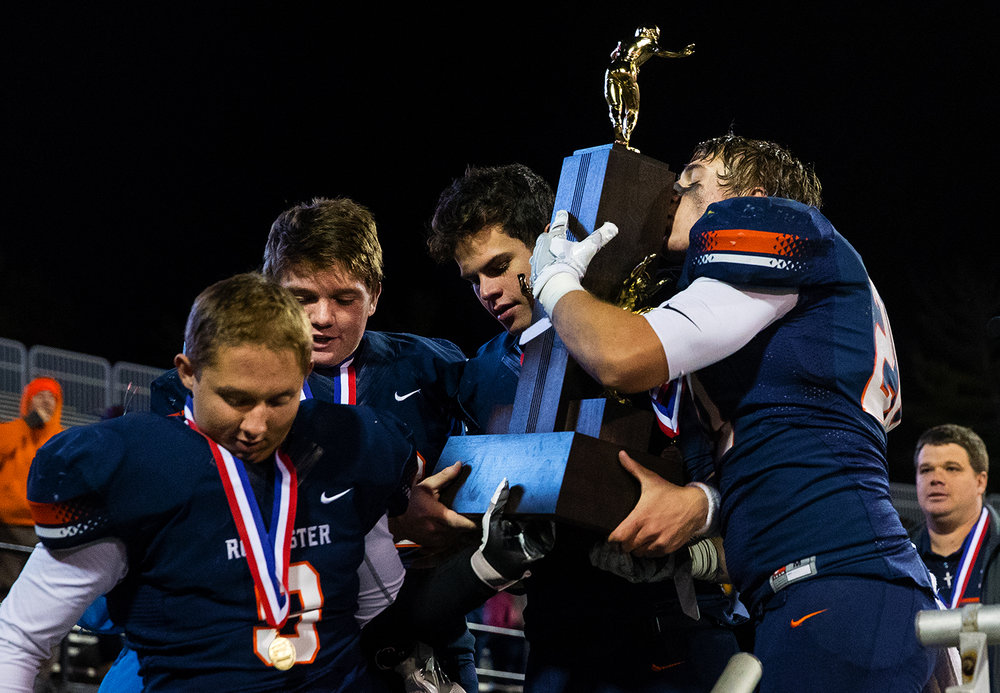 Rochester's Chase Kuntzman kisses the trophy as his teammates bring it down from the podium after the Rockets defeated Johnsburg during the Class 4A championship game at Memorial Stadium in Champaign, Ill., Friday, Nov. 25, 2016.  Ted Schurter/The State Journal-Register