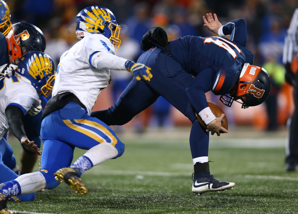 Rochester quarterback Josh Grant (14) gets tripped up by Johnsburg's Jack Kegel (5) after taking off on a run in the first quarter during the IHSA Class 4A State Championship at Memorial Stadium, Friday, Nov. 25, 2016, in Champaign, Ill. Justin L. Fowler/The State Journal-Register