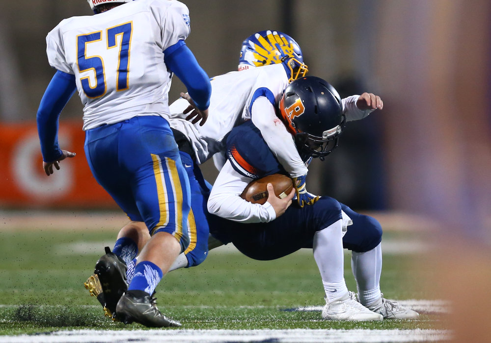 Rochester quarterback Nic Baker (19) is sacked by Johnsburg's Jack Kegel (5) in the second quarter during the IHSA Class 4A State Championship at Memorial Stadium, Friday, Nov. 25, 2016, in Champaign, Ill. Justin L. Fowler/The State Journal-Register