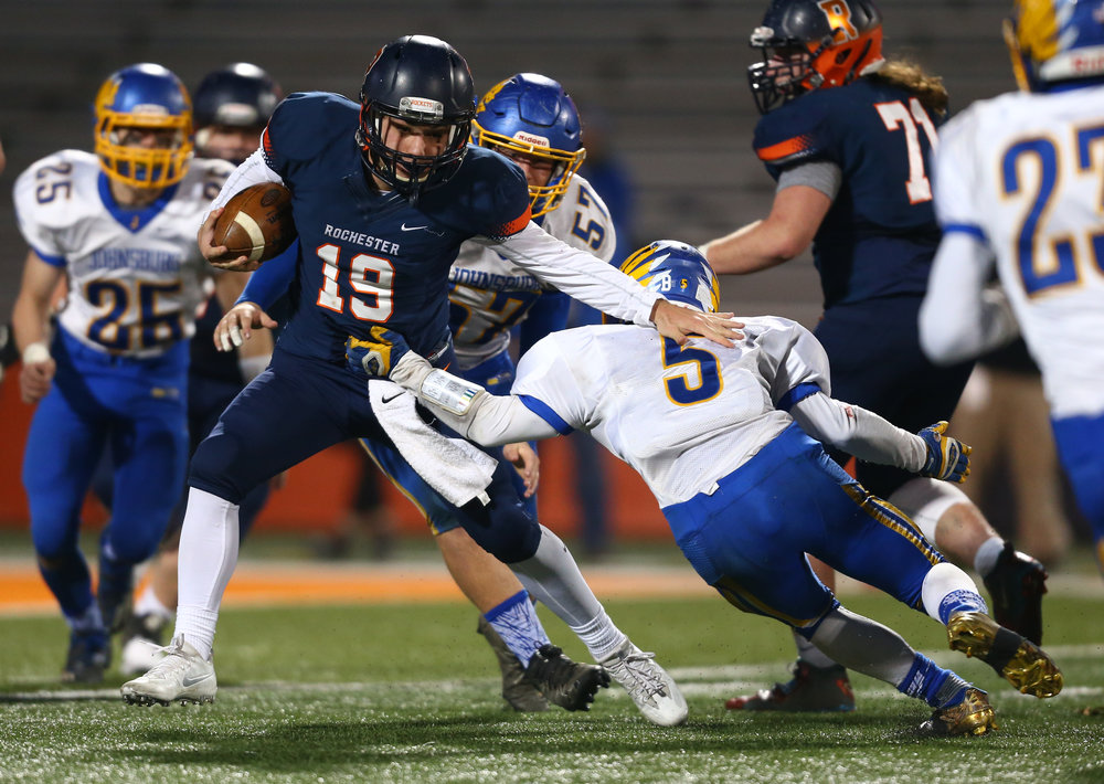 Rochester quarterback Nic Baker (19) tries to evade Johnsburg's Jack Kegel (5) on a rush in the second half during the IHSA Class 4A State Championship at Memorial Stadium, Friday, Nov. 25, 2016, in Champaign, Ill. Justin L. Fowler/The State Journal-Register
