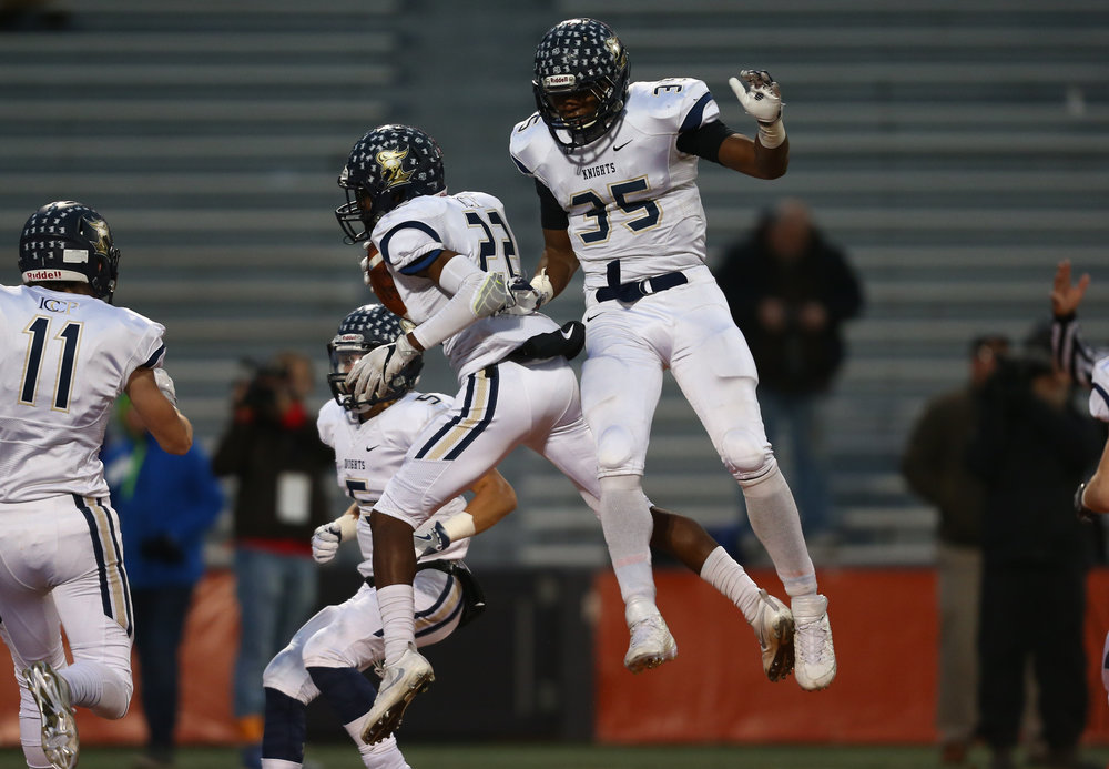 Elmhurst IC Catholic's Lazerick Eatman (22) jumps up to celebrate his touchdown with Elmhurst IC Catholic's Jordan Rowell (35) in the first quarter during the IHSA Class 3A State Championship at Memorial Stadium, Friday, Nov. 25, 2016, in Champaign, Ill. Justin L. Fowler/The State Journal-Register