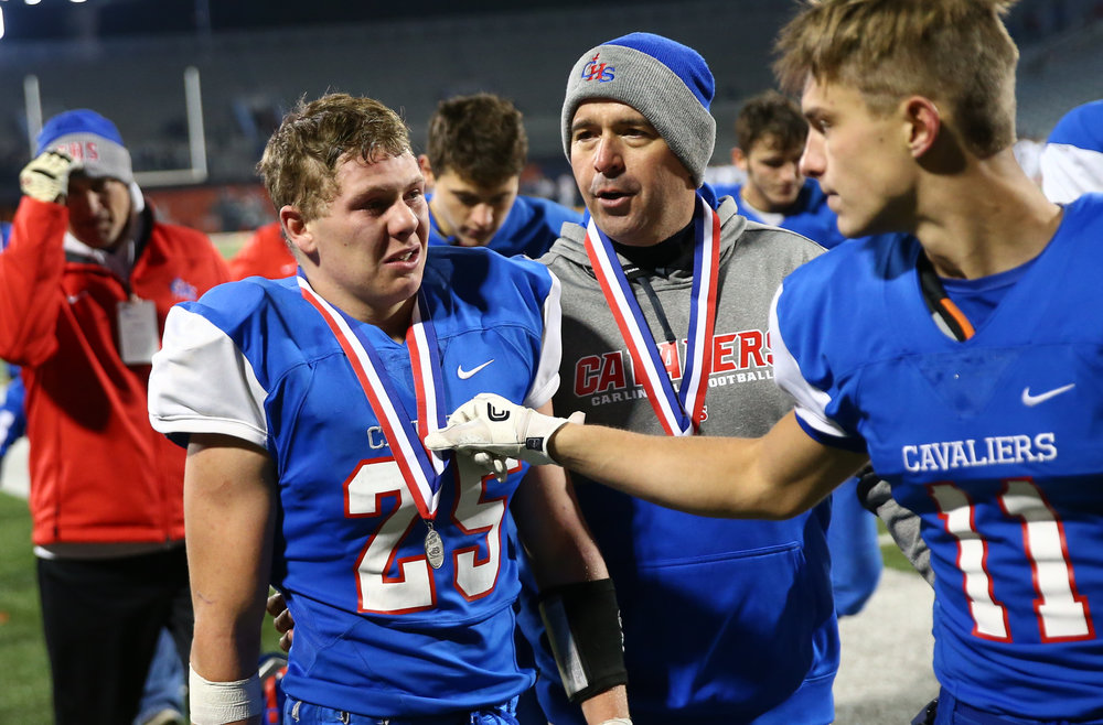 Carlinville football head coach Chad Easterday comes over to hug Carlinville's Dylan Chism (25) after the Cavaliers were defeated by Elmhurst IC Catholic 43-0 in the IHSA Class 3A State Championship at Memorial Stadium, Friday, Nov. 25, 2016, in Champaign, Ill. Justin L. Fowler/The State Journal-Register