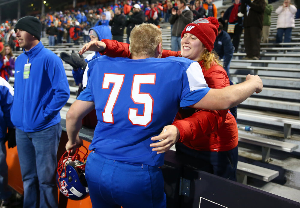 Kelsey Card comes over to hug her brother Carlinville's Daniel Card (75) after the Cavaliers were defeated by Elmhurst IC Catholic 43-0 in the IHSA Class 3A State Championship at Memorial Stadium, Friday, Nov. 25, 2016, in Champaign, Ill. Justin L. Fowler/The State Journal-Register