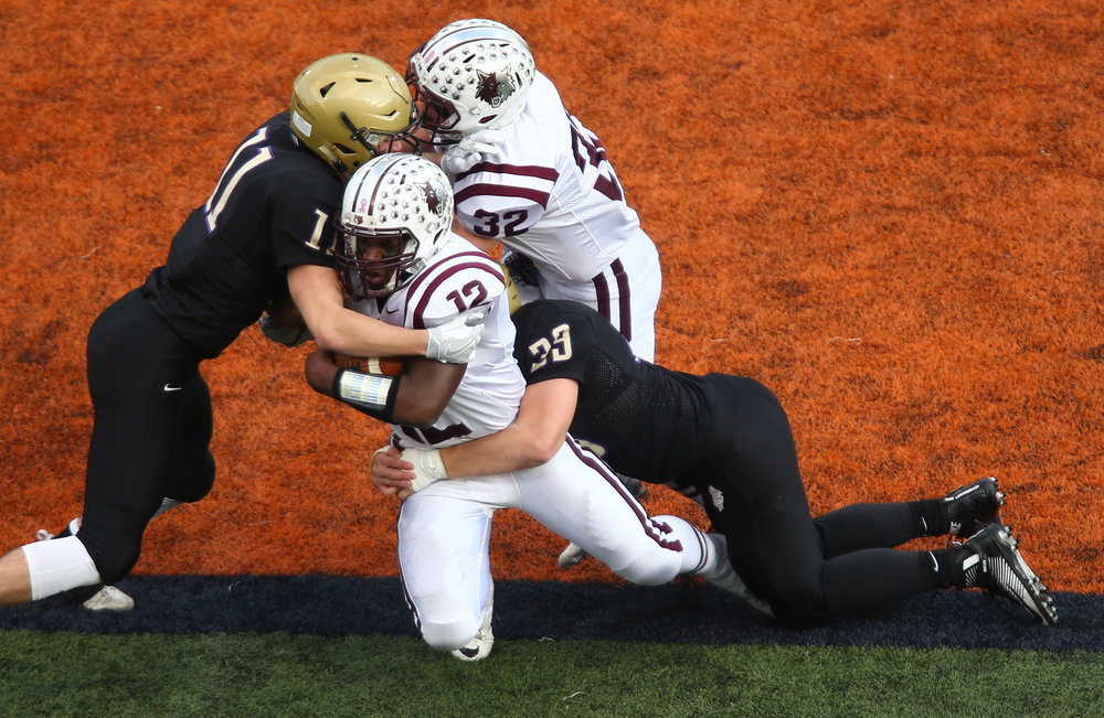 Crystal Lake Prairie Ridge's Emmanuel Ebirim (12) is brought down by Sacred Heart-Griffin's Jack Boll (11) and Sacred Heart-Griffin's Roger Dondanville (33) in the first half during the IHSA Class 6A State Championship at Memorial Stadium, Saturday, Nov. 26, 2016, in Champaign, Ill. Justin L. Fowler/The State Journal-Register