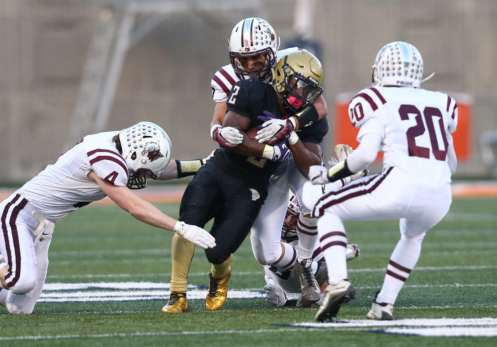 Sacred Heart-Griffin's Tremayne Lee (2) is swarmed by Crystal Lake Prairie Ridge's Daniel Renteria (7) and Crystal Lake Prairie Ridge's Nikolous Koelblinger (4) on a rush in the second half during the IHSA Class 6A State Championship at Memorial Stadium, Saturday, Nov. 26, 2016, in Champaign, Ill. Justin L. Fowler/The State Journal-Register