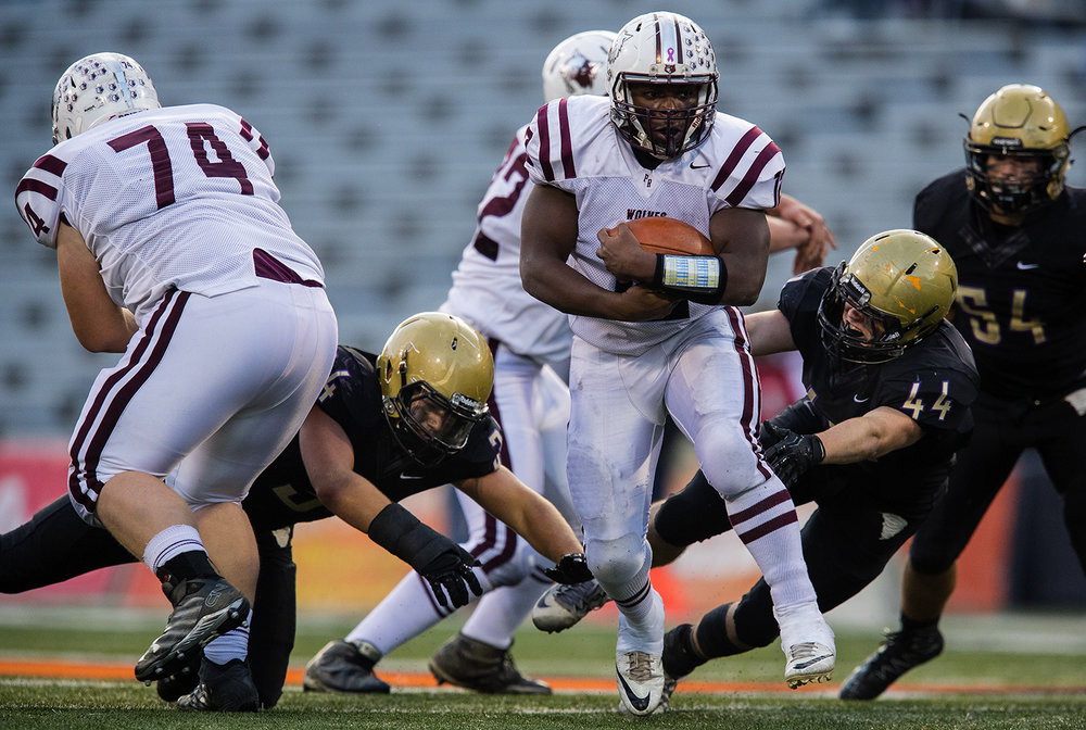 Prairie Ridge Benjamin Schultz breaks through a hole in the Sacred Heart-Griffin defense during the Class 6A championship game at Memorial Stadium in Champaign, Ill., Friday, Nov. 26, 2016.