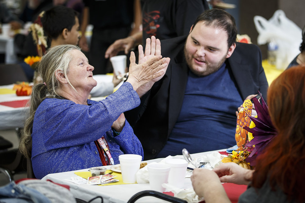 Peggy Duffey, left, gets a high five from Allen Andrus, center, after enjoying their meal during during the Lincoln Land chapter of ABATE's 30th Annual Charity Thanksgiving Meal at the parish hall of the Cathedral of the Immaculate Conception, Sunday, Nov. 20, 2016, in Springfield, Ill. Justin L. Fowler/The State Journal-Register