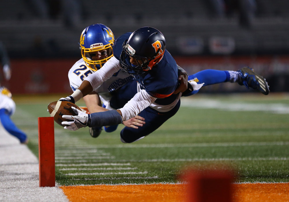Rochester's D'Ante Cox (1) dives into the end zone for a touchdown against Johnsburg's Austin Butler (25) in the second half during the IHSA Class 4A State Championship at Memorial Stadium, Friday, Nov. 25, 2016, in Champaign, Ill. Justin L. Fowler/The State Journal-Register