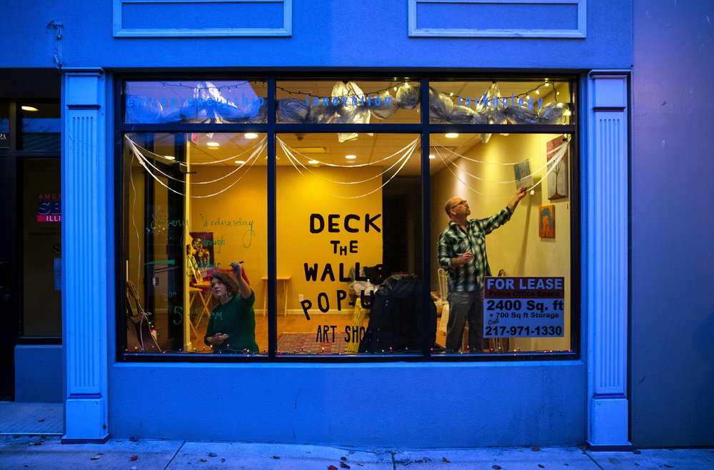 Clare Frachey writes a message on the window of the Deck the Walls Pop Up Show as artist Vince Merriman hangs some of his work on the wall Wednesday, Nov. 30, 2016. The storefront at 512 E. Adams in downtown Springfield will be open throughout the 2016 Downtown Holiday Walks from 5- 8 p.m.. Ted Schurter/The State Journal-Register