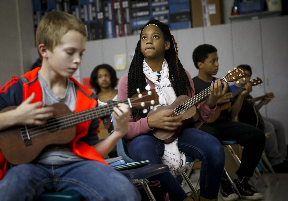 "Clinesha Toliver, center, a 7th grader at Ball Charter School, watches the chord progressions for the song ""Imagine"" by The Beatles as she and her and classmates learn the song on ukuleles during music class at Ball Charter School, Thursday, Dec. 1, 2016, in Springfield, Ill. Justin L. Fowler/The State Journal-Register"