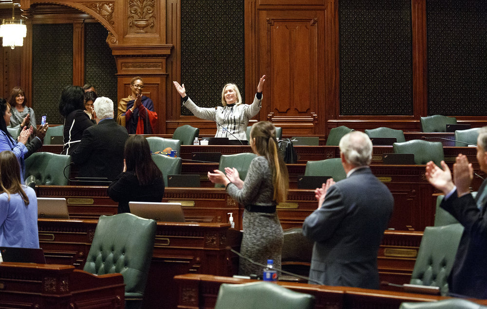 "Rep. Kate Cloonen, D-Kankakee, is applauded by her House colleagues after she sang ""God Bless America"" by request during a break in floor debate at the Capitol Thursday, Dec. 1, 2016. Cloonen, a former music teacher who lost her bid for re-election, agreed to sing only if everyone joined her. Rich Saal/The State Journal-Register"