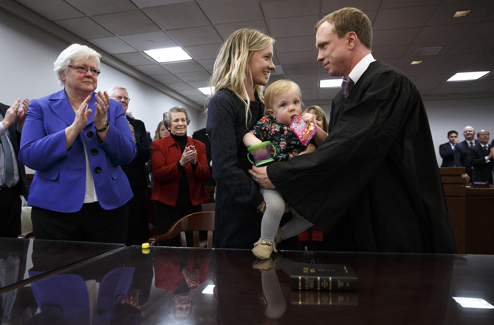 Judge Ryan Cadagin, right, takes his daughter, Patsy, from his wife Katherine, center, as a crowd of supporters including his mother Kathy Cadagin, left, stand to congratulate him after being sworn in as a circuit judge for the 7th Judicial Circuit at the Sangamon County Complex, Monday, Dec. 5, 2016, in Springfield, Ill. Justin L. Fowler/The State Journal-Register