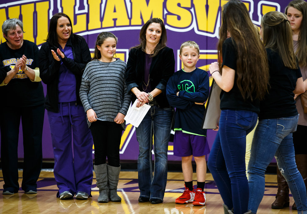 Julie Root, center, the wife of David Root, along with their children, Mia, left, and Dalton, right, are presented with a framed print by the volleyball and basketball teams of the newly dedicated David J. Root Court during a ceremony at Williamsville High School, Tuesday, Dec. 6, 2016, in Williamsville, Ill. David Root passed away in September and was the Superintendent of Williamsville-Sherman School District and played an instrumental role in the renovations the gym received in 2014. Justin L. Fowler/The State Journal-Register