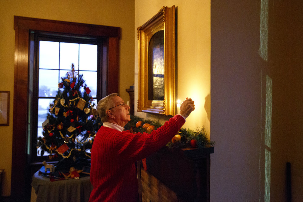 Larry Buhl, a volunteer, lights a candle at the Elijah Iles House before the annual candlelight tour of the historic home Friday, Dec. 9, 2016. The house is the oldest in Springfield and is decorated in the style of Christmas during different times in the 19th and 20th centuries.  The candlelight tours return Feb. 16 and 17 from 5-8 p.m. Rich Saal/The State Journal-Register