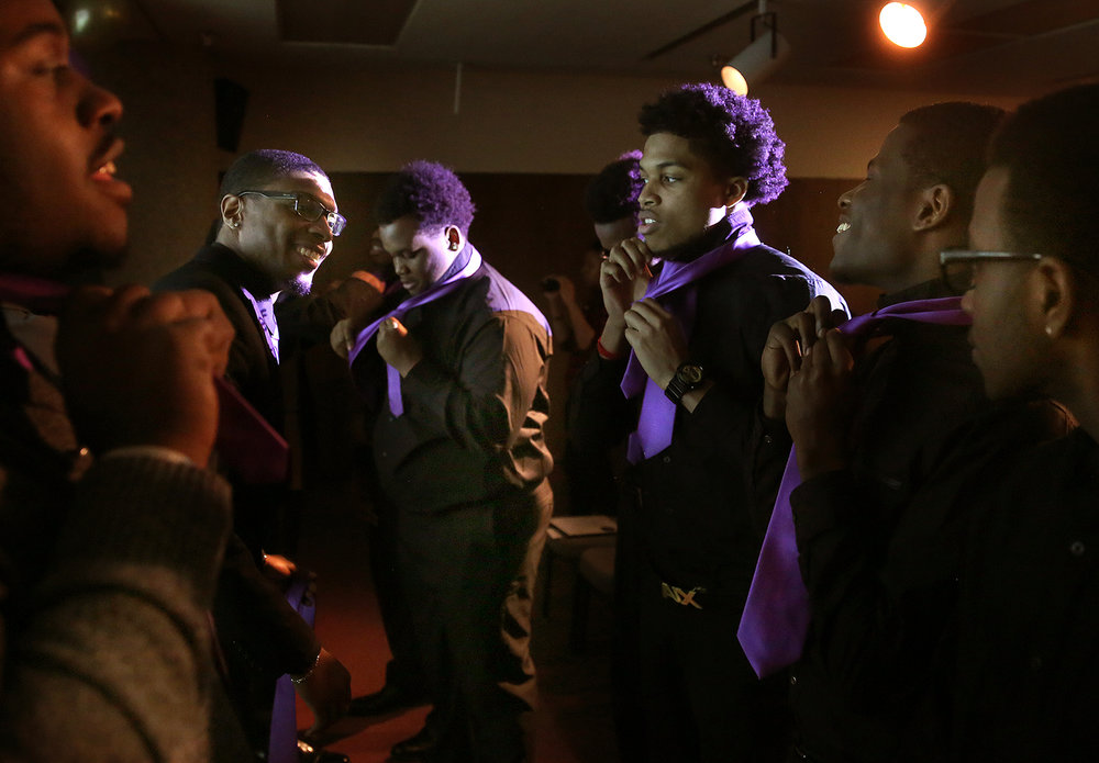 Members of the Black Male Collegiate Society put on purple ties presented to them during an induction ceremony Friday, Feb. 5, 2016 at the University of Illinois Springfield. The society promotes brotherhood, fidelity and achievement and the ceremony was held in conjunction with Black History Month events on the campus.  David Spencer/The State Journal-Register