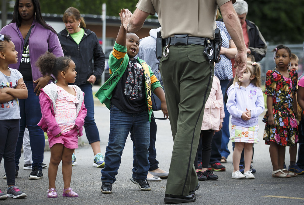 Jamari Kerr, 5, center, gets a high five from Illinois State Police Trooper Sean Ramsey, the District 9 Safety Education Officer, after watching a demonstration on the importance of wearing a seat belt during Big Truck Day at the Early Learning Center Friday, May 20, 2016.  Justin L. Fowler/The State Journal-Register