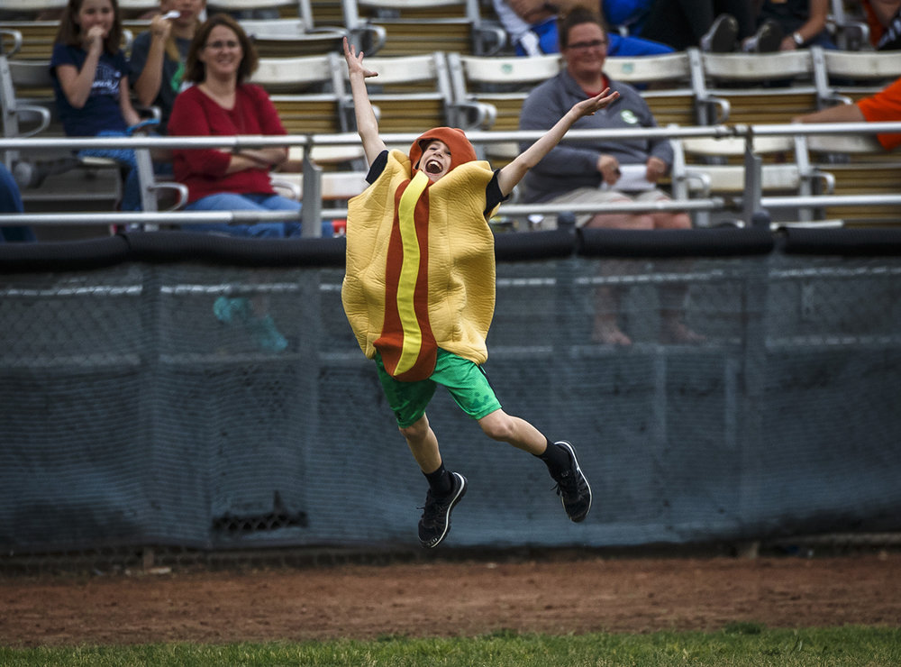 The Hot Dog celebrates winning the race around the bases against the Ketchup and the Mustard between innings of the Springfield Sliders' home opener at Robin Roberts Stadium Friday, May 27, 2016.  Justin L. Fowler/The State Journal-Register