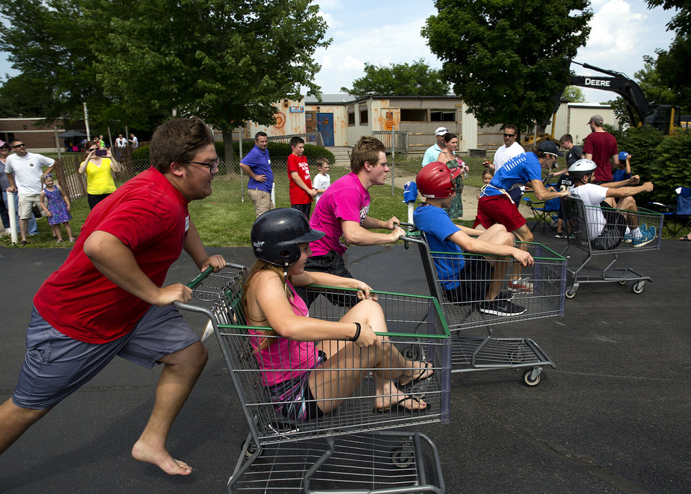 A shopping cart race was one of the ways friends and alumni of Lutheran High School celebrated the demolition of the school's quad campus, a series of temporary classrooms installed more than 30 years ago, during a demolition party and picnic Saturday, June 11, 2016.  Rich Saal/The State Journal-Register