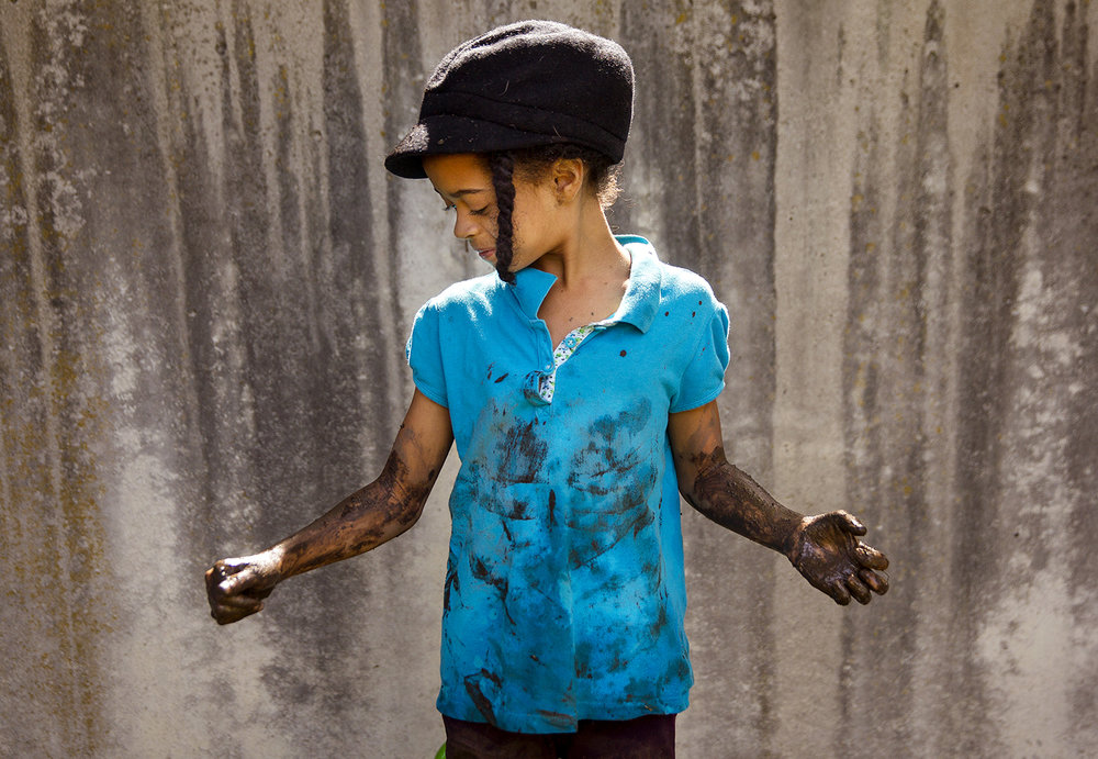 Te'Asia Durbin glances at the mud coating her arms after climbing out of a mud hole at Adventurous Learning daycare in Springfield during International Mud Day June 29, 2016.  Ted Schurter/The State Journal-Register