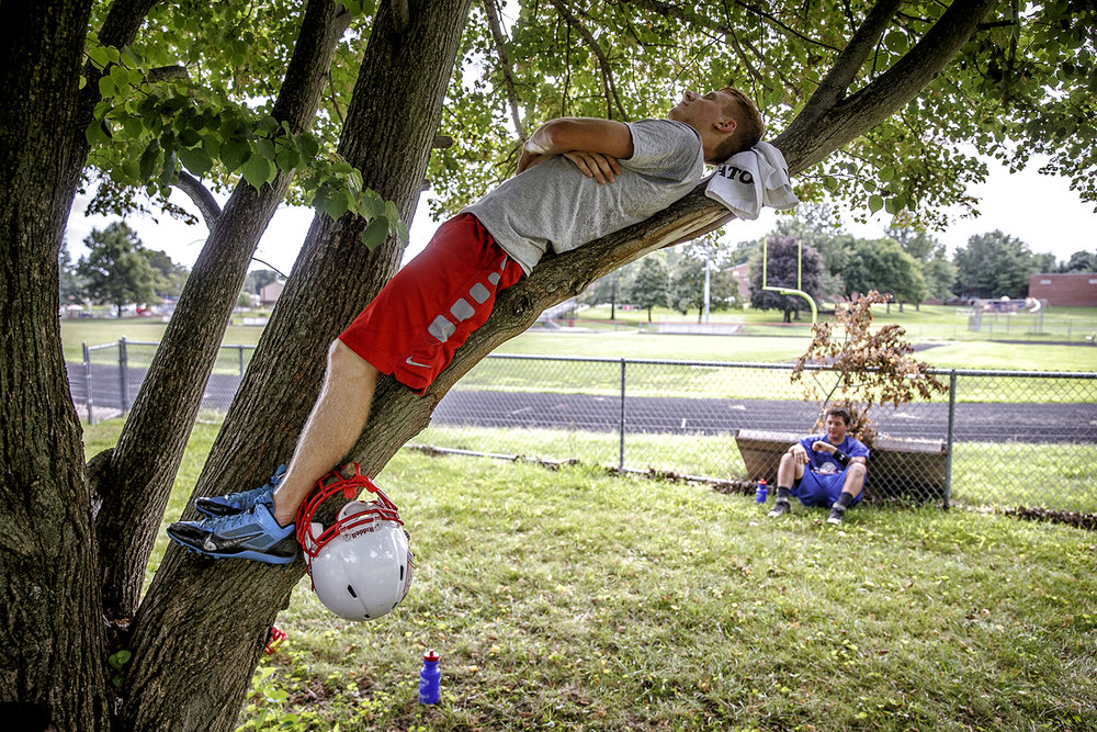 Trenton Eckert finds a bit of quiet in the branches of a tree when the football team takes a break on the first day of practice at Pawnee High School Monday, Aug. 8, 2016.  Justin L. Fowler/The State Journal-Register