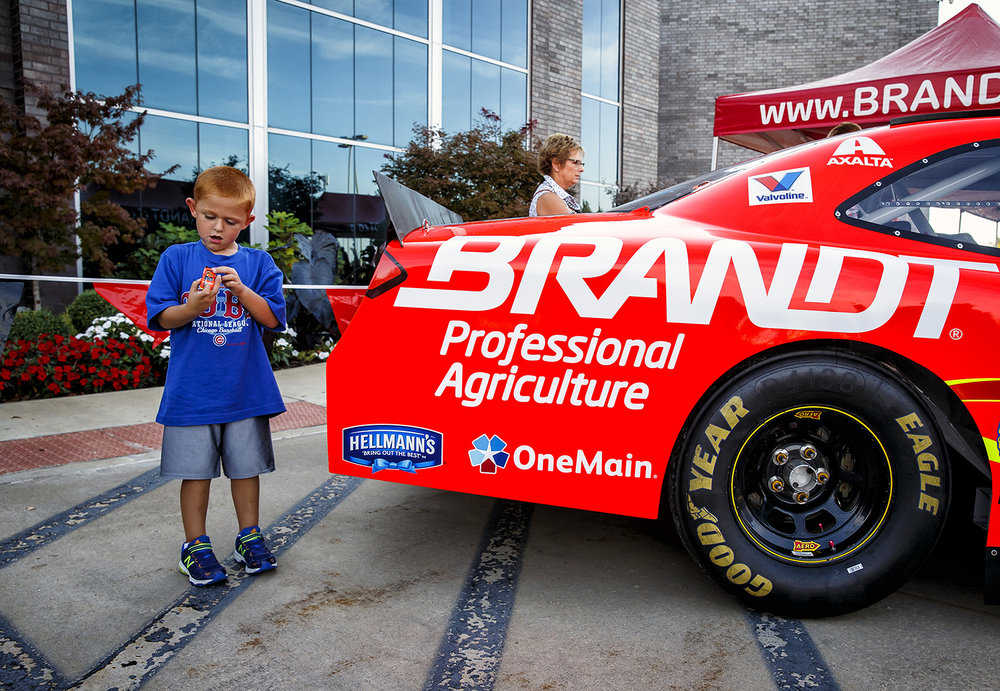 Brindan Graham, 5, of Jacksonville, compares his die-cast model of Justin Allgaier's Brandt sponsored #7 NASCAR Xfinity Series stock car with the real thing on display at the Brandt Headquarters, Thursday, Sept. 22, 2016.  Justin L. Fowler/The State Journal-Register