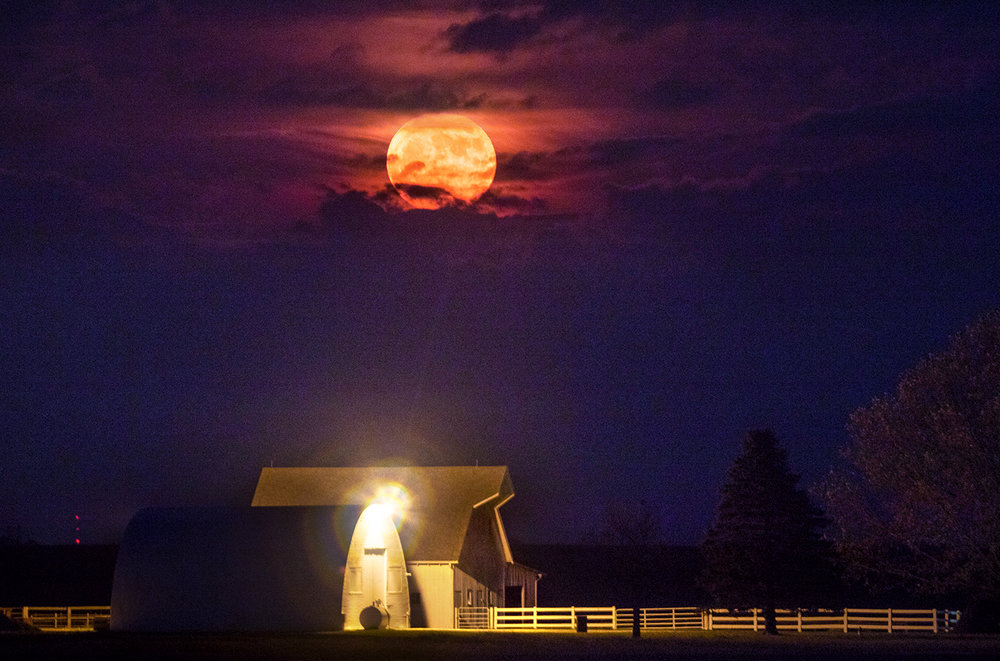 A super moon breaks through a low layer of clouds as it rises above a farmstead south of Mt. Auburn Monday, Nov. 14, 2016. The moon was the closest full moon to earth since 1948, and it won't be as close again until 2034.  Ted Schurter/The State Journal-Register