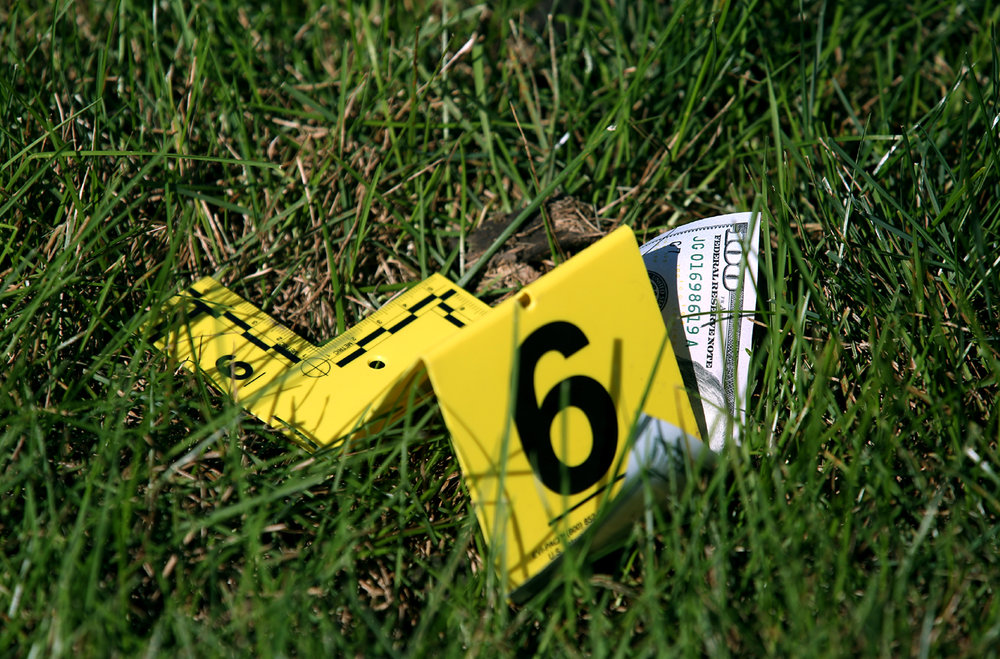 A police evidence marker rests on a $100 bill laying in the grass near the entrance to Chase Bank at 2801 Greenbriar Rd. Friday, Oct. 7, 2016. A man police believe may have been involved in two other bank robberies in the area, walked into the bank and demanded money and apparently dropped some as he fled the bank.  Rich Saal/The State Journal-Register