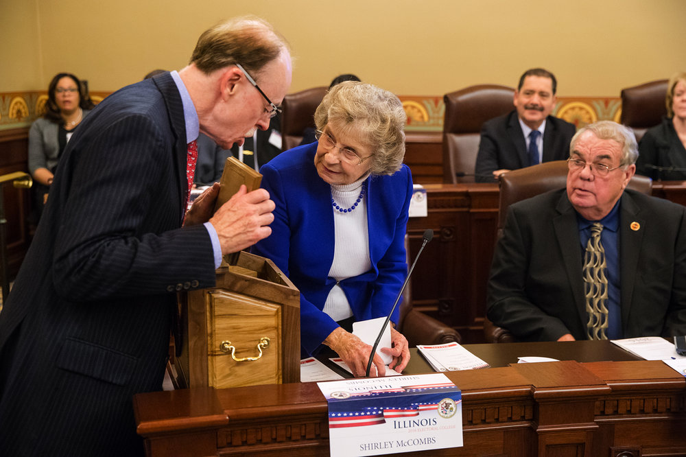 Tim Mapes, ‎Executive Director at Democratic Party of Illinois, peeks into the Illinois Electoral College Ballot Box as elector Shirley McCombs counts the ballots in Capitol Room 118 Monday, Dec. 19, 2016. Illinois members of the Electoral College cast their ballots for Hillary Clinton for president. Ted Schurter/The State Journal-Register