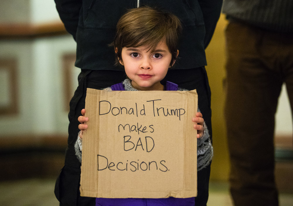Four-year-old Ember Wilson holds a sign while her family protests against Donald Trump's presidency in the rotunda of the Illinois Capitol building Monday, Dec. 19, 2016. A group of protesters gathered to protest before members of the Illinois Electoral College cast their ballots for Hillary Clinton for president. Ted Schurter/The State Journal-Register