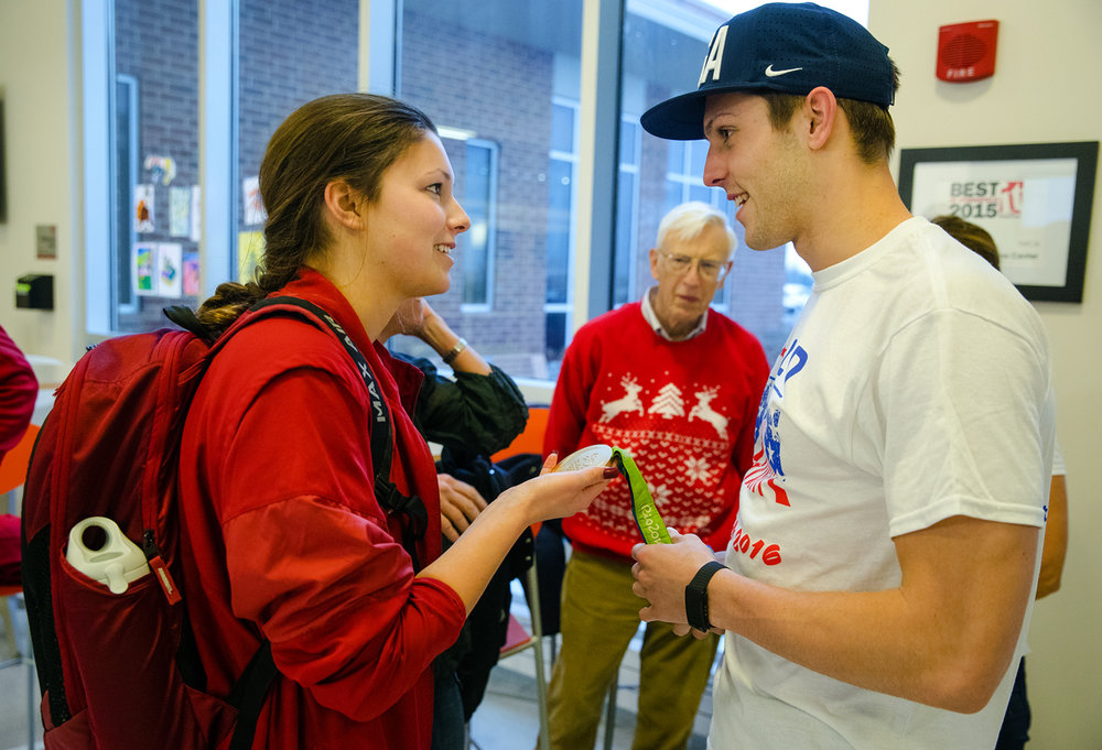 "Annah Carney hefts Ryan Held's 2016 Olympic gold medal as they visit before a ceremony observing the donation of $4,000 to the Springfield YMCA Strong Kids on behalf of Held and Outbreak Designs Screenprinting at the Gus & Flora Kerasotes YMCA Friday, Dec. 23, 2016. Outbreak initially planned on donating money raised selling their ""Held to a Higher Standard of Excellence"" t-shirts to the Held family to offset their travel expenses to the games. The Held family requested that the money go to the YMCA, who Held swam for as a youth, instead. Held was a member of the gold medal winning Men's 4x100 Freestyle Relay Finals in the 2016 Olympic Games. Ted Schurter/The State Journal-Register"