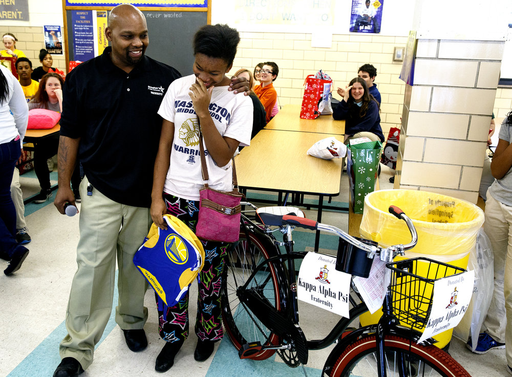 "Jas 'Min Bivins was overwhelmed when she was told she was the recipient of a new Huffy Cruiser bicycle at the 50 Smiles Christmas gift event at Washington Middle School Wednesday, Dec. 21, 2016. Darryl Williams, left, is a security guard at the school who started the program 10 years ago, which presented gifts to 80 students. ""I love riding a bike, it's like, amazing,"" Bivins said. Rich Saal/The State Journal-Register"