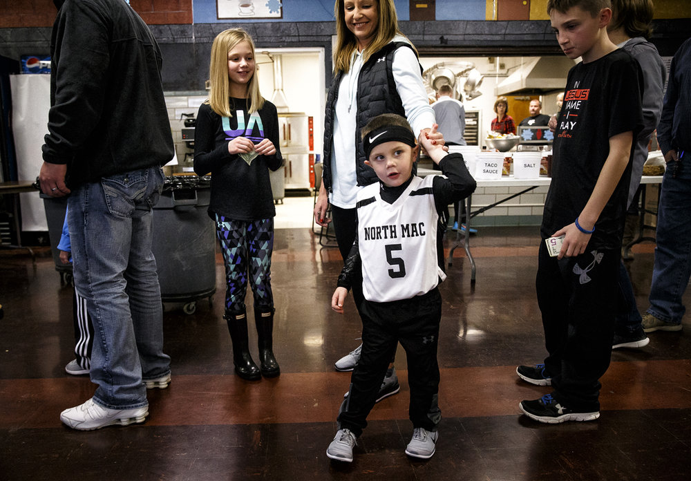 Braxton Earley, 4, center, twirls underneath the arm of his mother, Brooke Earley, as he waits in line for a bag of popcorn at the concession stands during the 66th annual Waverly Holiday Basketball Tournament at Waverly Elementary School, Monday, Dec. 26, 2016, in Waverly, Ill. Earley came dressed to support the North Mac Panthers and his favorite player #5 Grant Graham as they took on Tri-City. Justin L. Fowler/The State Journal-Register