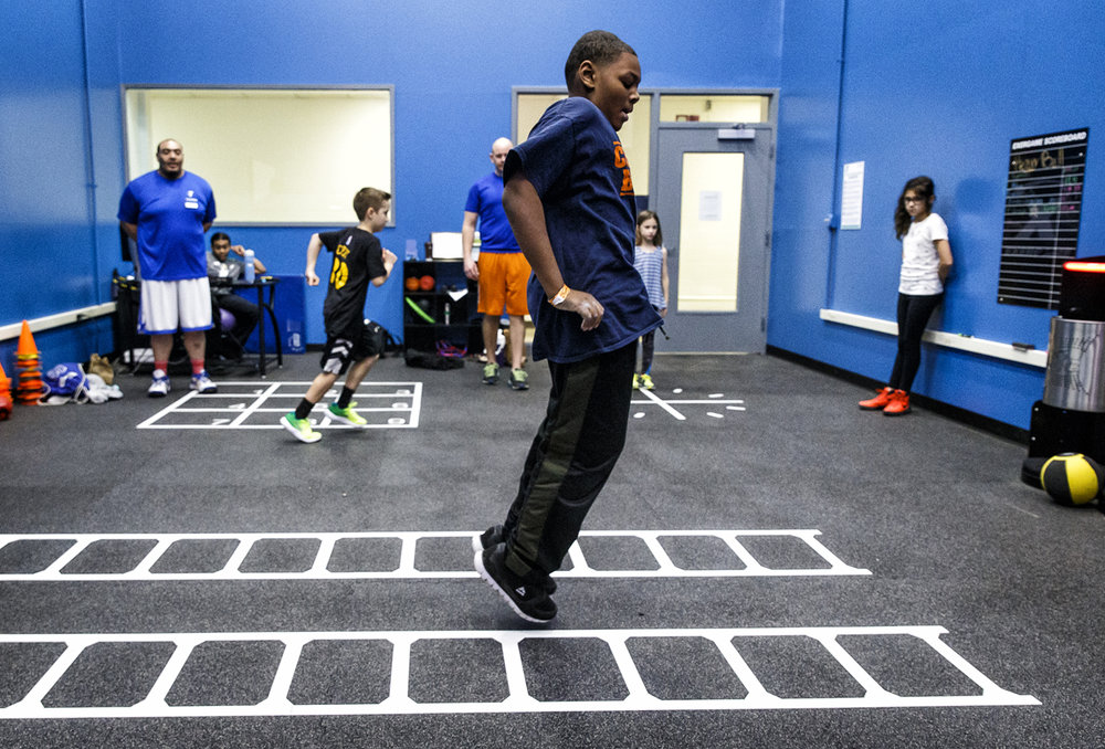 "Zion Akers, 12, leaps through a ladder agility obstacle  while going through a timed group of Exergames for the Functional Fitness for Youth program in the Youth Fitness Center at the Downtown YMCA, Tuesday, Dec. 27, 2016, in Springfield, Ill. The program is the first group exercise for youth in the new Youth Fitness Center and is aimed at improving mobility, strength and agility skills. ""We want to combat physical illiteracy, which means a lot of times kids go to gym class and they're not confident,"" said A.J. Akers, associate fitness director for the Downtown YMCA. ""We want to reinforce skills they were born with, crawling, jumping and running. A lot times when they're sitting on the couch all day they loose some of that ability."" Justin L. Fowler/The State Journal-Register"