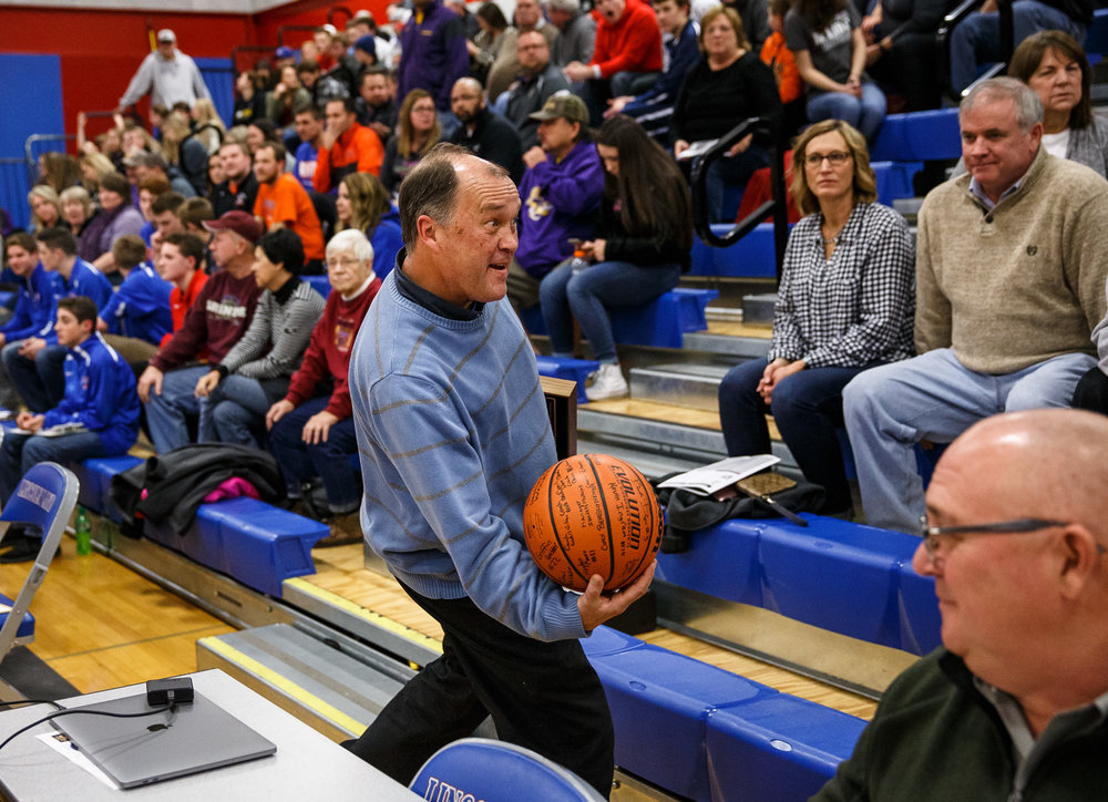 "State Journal-Register sports reporter Dave Kane pretends to toss a basketball into the crowd after being honored with the ""Friend of the County"" award prior to the championship game of the Sangamon County Tournament at Cass Gymnasium, Friday, Jan. 13, 2017, in Springfield, Ill. Justin L. Fowler/The State Journal-Register"