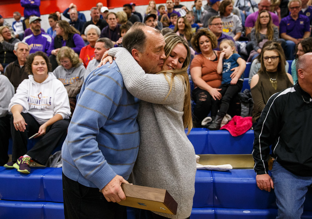 "State Journal-Register sports reporter Dave Kane gets a hug from his daughter, Charlotte, after being honored with the ""Friend of the County"" award prior to the championship game of the Sangamon County Tournament at Cass Gymnasium, Friday, Jan. 13, 2017, in Springfield, Ill. Justin L. Fowler/The State Journal-Register"
