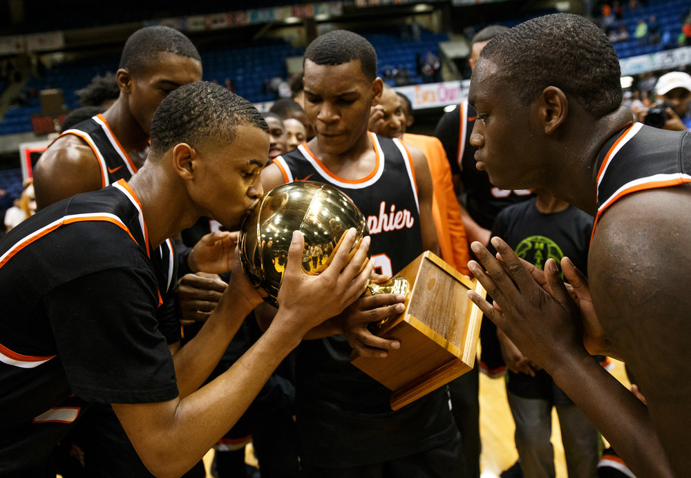 Lanphier's Cardell McGee (2) gets a kiss on the championship trophy after the Lions defeated Southeast 60-49 in the championship game of the Boys City Basketball Tournament at the Prairie Capital Convention Center, Saturday, Jan. 21, 2017, in Springfield, Ill. Justin L. Fowler/The State Journal-Register