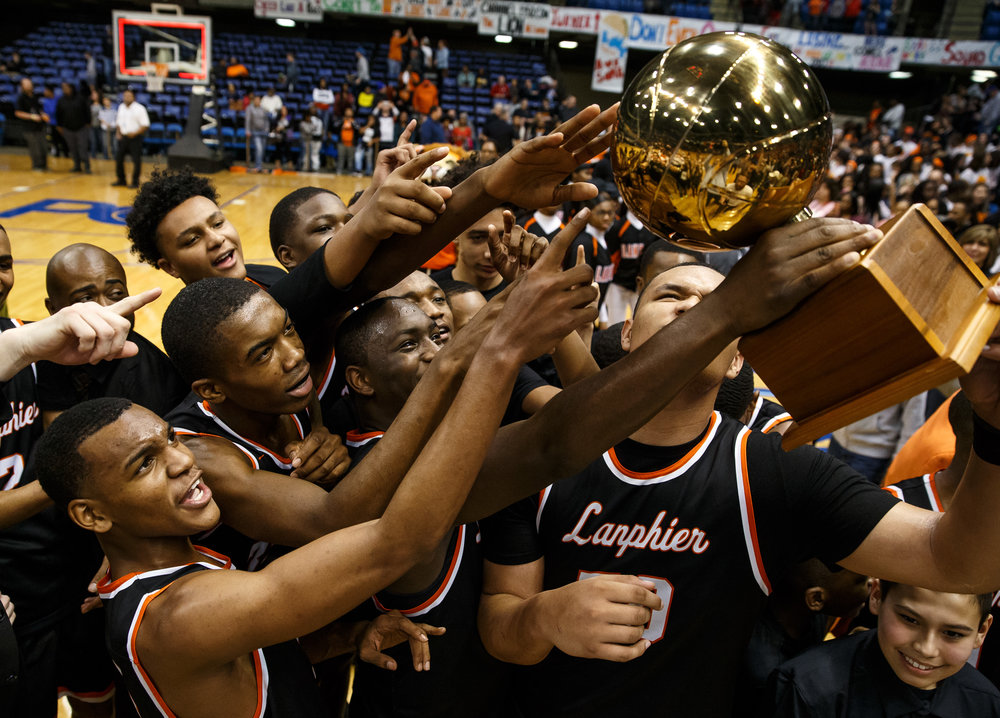 The Lanphier Lions check out their reflection in the championship trophy after they defeated Southeast 60-49 in the championship game of the Boys City Basketball Tournament at the Prairie Capital Convention Center, Saturday, Jan. 21, 2017, in Springfield, Ill. Justin L. Fowler/The State Journal-Register