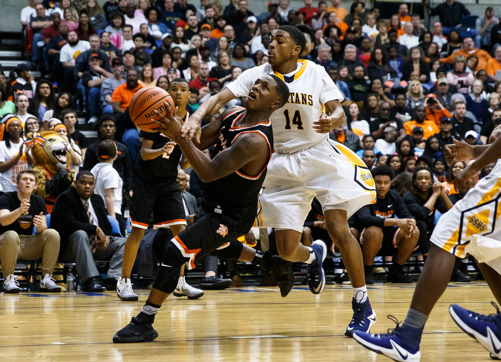 Lanphier's Yaakema Rose (1) draws the foul from Southeast's Trevyon Williams (14) driving to the basket in the fourth quarter of the championship game of the Boys City Basketball Tournament at the Prairie Capital Convention Center, Saturday, Jan. 21, 2017, in Springfield, Ill. Justin L. Fowler/The State Journal-Register